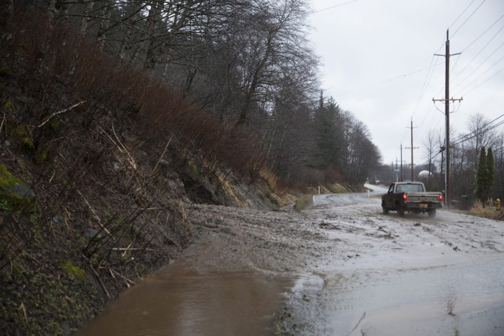 A truck drives through an open lane after a mudslide on Monday, December 11, 2017, in Juneau, Alaska. The slide happened near the intersection of Mill Street and Thane Road south of downtown Juneau. (Rashah McChesney/Alaska's Energy Desk)